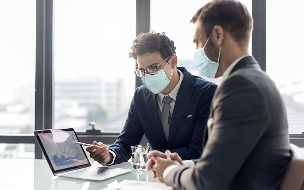 Office in new normal, men wearing medical mask covid 19